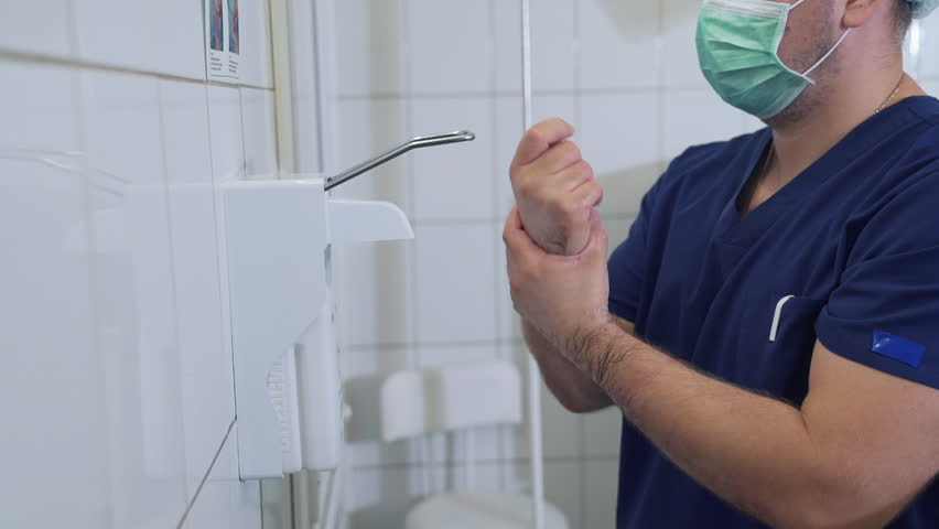 Doctor disinfects and washing his hands dry before entering the operating room. Surgical hand disinfection. Emergency care. Surgery detail in hospital or clinic