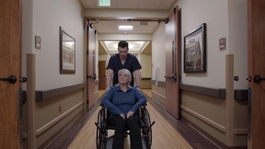Steadicam shot of a male nurse pushing a senior woman in a wheelchair | Shutterstock HD Video #1010041355