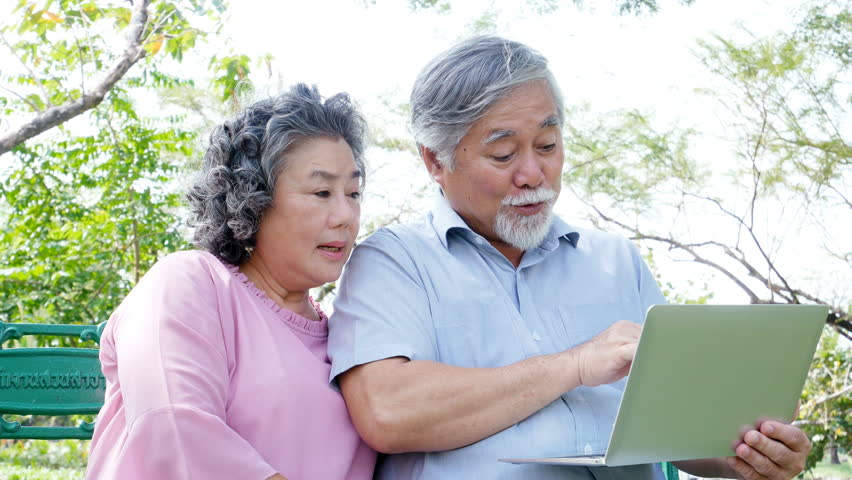 Asian couple elder people relax at park together. Elder people using laptop with happy emotion. People lifestyle concept