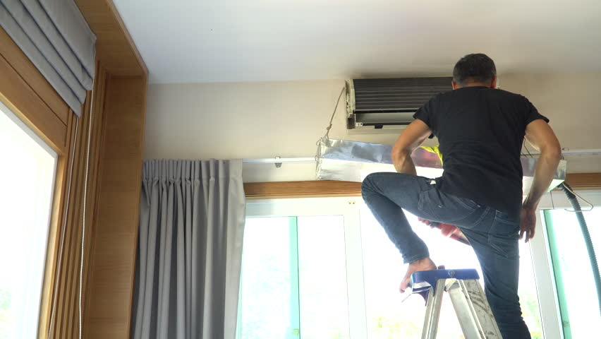 Technician man repairing ,cleaning and maintenance Air conditioner on the wall in bedroom.On site home service,Business concept.