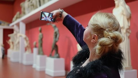Woman makes selfie by smart-phone near sculptures in museum
