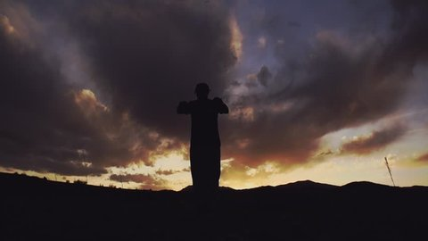 Acrobat in silhouette does beautiful x out backflip on mountain at sunset in slow motion. Shot on Sony FS700 240 FPS