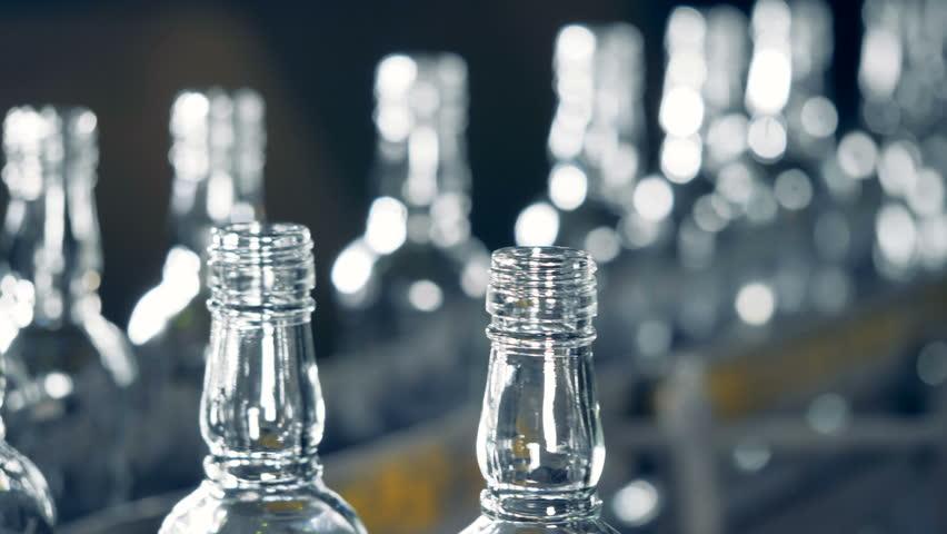 Row of glass bottles on a conveyor, close up. | Shutterstock HD Video #1010058815