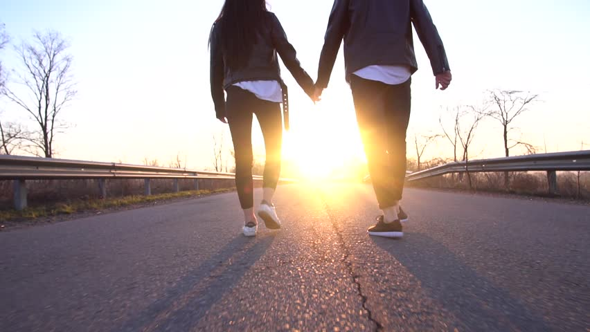 Slow motion as a couple holds hands on the road in the morning | Shutterstock HD Video #1010066855