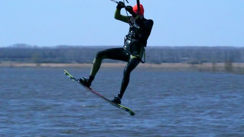 SLOW MOTION: A male kiteboarder rides on a board along the river. He performs various exercises while moving on water. Water still muddy river, the ice has just melted. Sunny spring day.