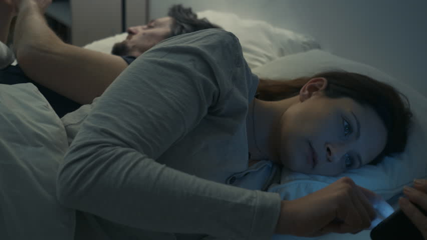 Couple in bed at home in the evening- after argument with distance and on their smartphones.