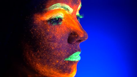Close up portrait of fashion model woman with braids in neon light. Fluorescent makeup glowing under UV black light. Night club, party, halloween psychedelic concepts.