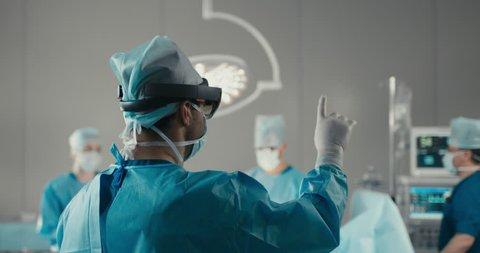 MED Team of surgeons using augmented reality holographic hololens headset while operating in modern operation theater. 4K UHD 60 FPS SLO MO