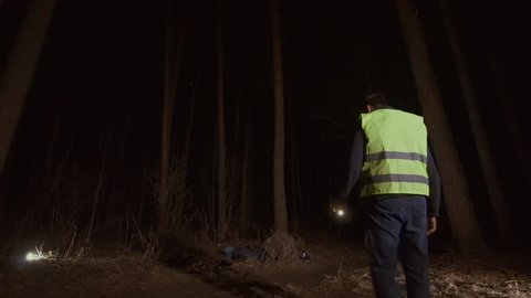 man and woman volunteers in a reflective waistcoat found a corpse in the forest