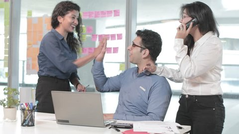 A mixed gender group of young office workers are happy and celebrating the achievement. Smiling, cheerful young team consist of male and females celebrating success after completing critical task