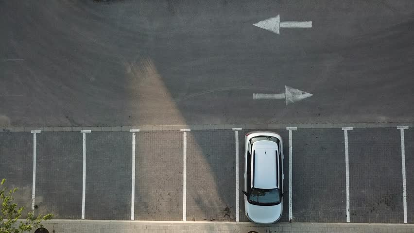 Aerial View a car pulling out of a parking in reverse and driving away  | Shutterstock HD Video #1010118365