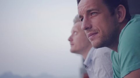 Two friends of men sail by ferry to meet a fresh wind, stand on the deck enjoying the wind. slow motion. 1920x1080. full hd