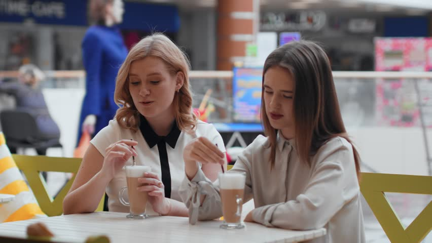 Young women drinking coffee and communicating in cafe. | Shutterstock HD Video #1010135015