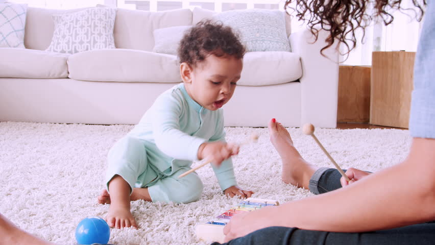 Black toddler playing xylophone with his mum in sitting room