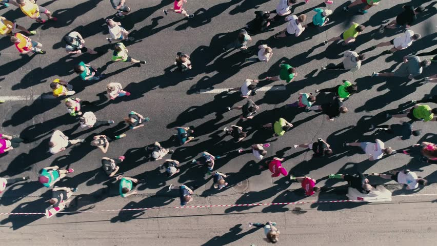 4K Aerial drone fooage. Marathon running on street. Top view close up rotate camera