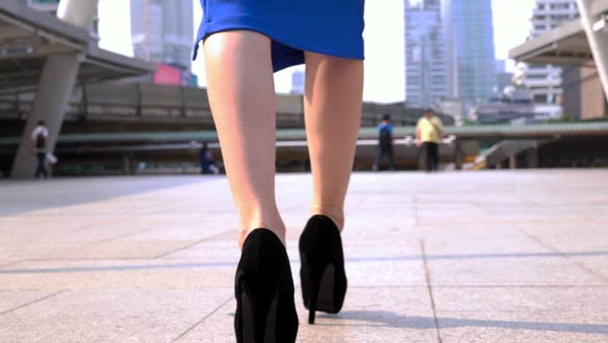 Woman's legs in high heel shoes walking on road slow motion.   Shutterstock HD Video #1010154125