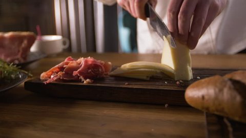 Slicing cheese for Spanish dishes-tapas. Cook work of the highest qualification.