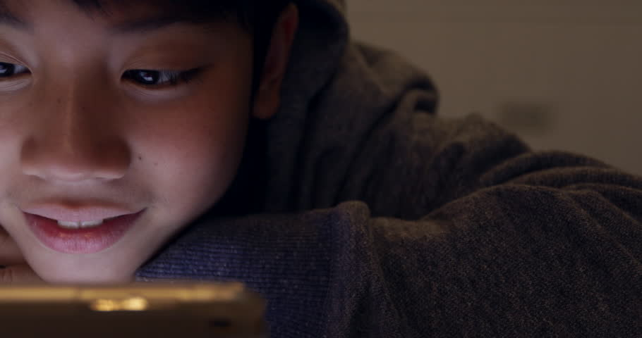 Close up of cute asian boy using tablet computer ,Young teenage boy playing games on digital tablet with smile face .