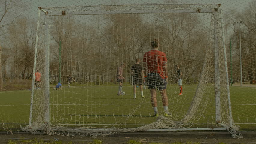 Opposing team attacking opponent goal , strikers dribbling, passing and taking a shot on goal during football training session on soccer field. Young goalkeeper making a save after shot during game. | Shutterstock HD Video #1010180855