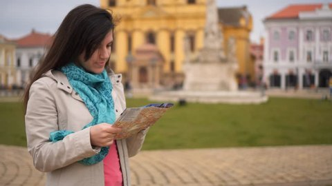 Girl looking at map of Timisoara. Young brunette woman standing on a city square in Timisoara, Romania, looking at the map.