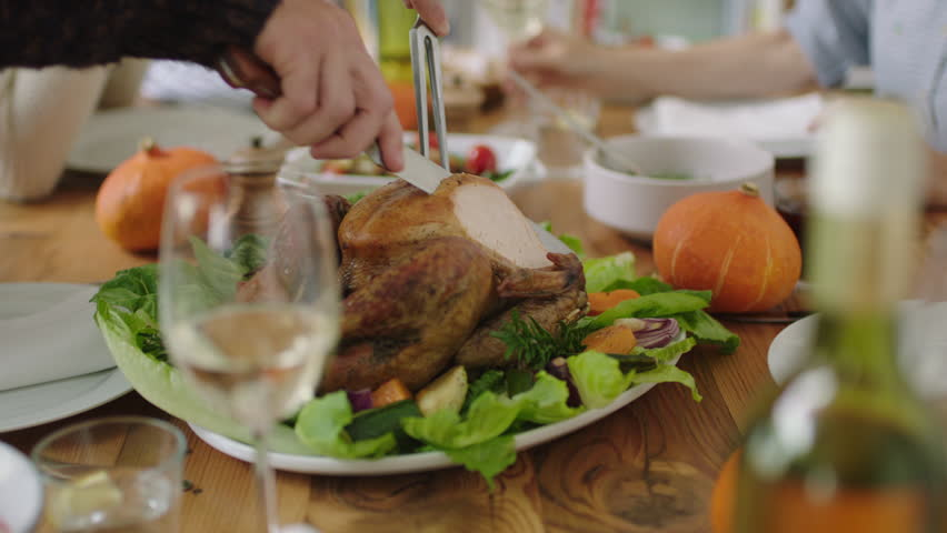 Close up of family enjoying thanksgiving lunch together cutting delicious turkey celebrating homemade cooked meal healthy lifestyle   Shutterstock HD Video #1010187035