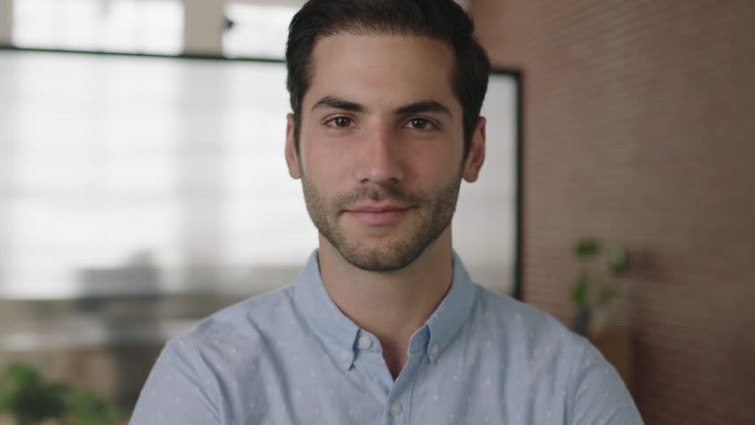 Close up portrait of young attractive middle eastern businessman looking at camera smiling confident in office workspace background real people series | Shutterstock HD Video #1010187125
