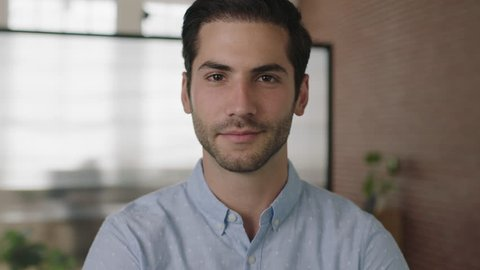 close up portrait of young attractive middle eastern businessman looking at camera smiling confident in office workspace background real people series