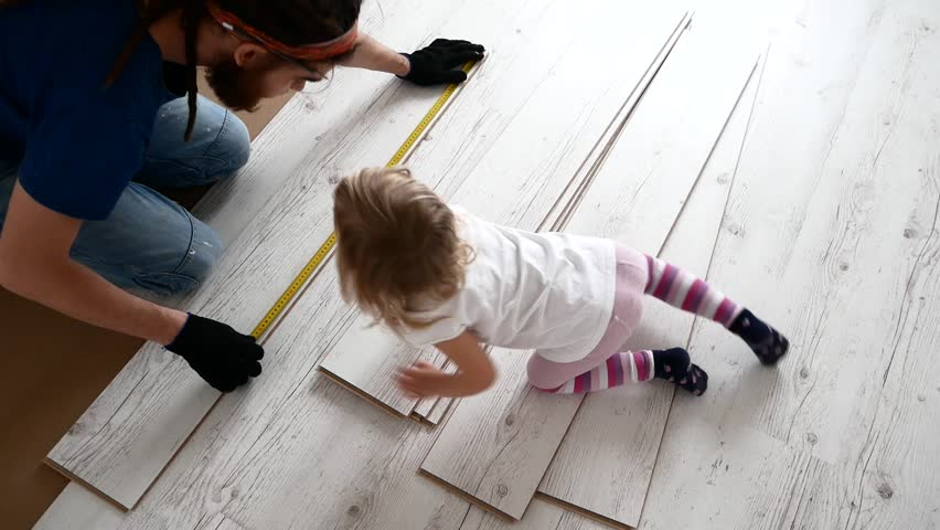 Dad and daughter are doing repairs in the apartment. Laminate laying   Shutterstock HD Video #1010187575