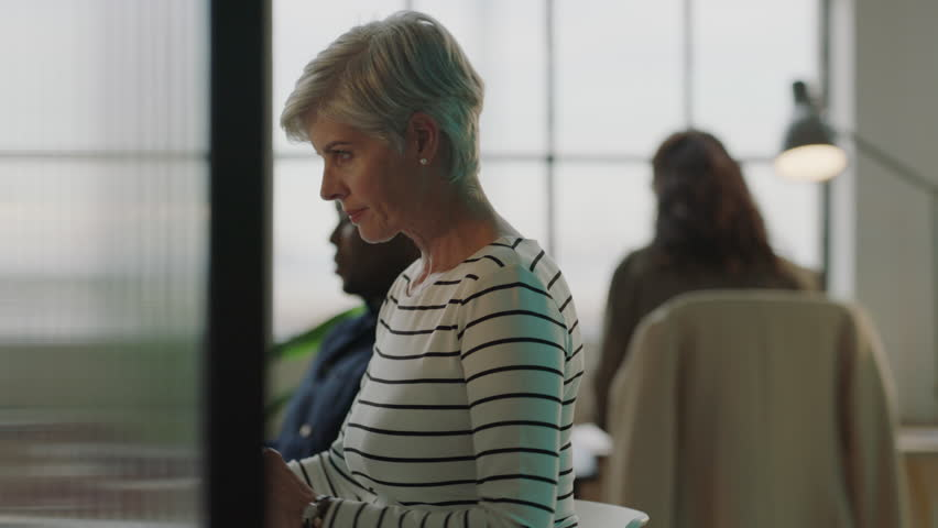 Mature business woman typing using computer sending email networking diverse team in busy office workspace | Shutterstock HD Video #1010189345