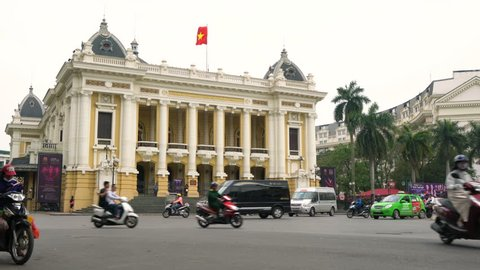 TRAFFIC AND PEOPLE OUTSIDE HANOI OPERA HOUSE, HANOI , VIETNAM –  2 APRIL 2018: Scooters, cars, traffic and people outside Hanoi Opera House, Hanoi, Vietnam