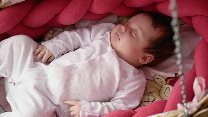 Cute newborn baby sleeping in swinging wattled cradle. Middle shot   Shutterstock HD Video #1010198855