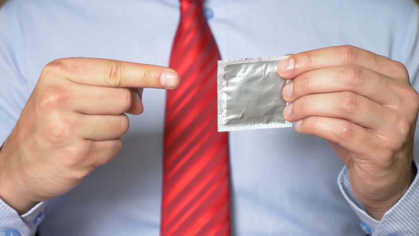 4k, slow-motion, close-up. men's hands hold a packaged condom. The concept of safe sex and contraception.