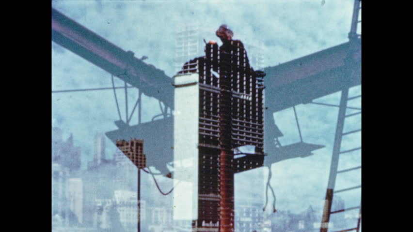 1950s: Skyscraper construction site. Workers and men gather at the top of the skyscraper. Men raise flag on top of skyscraper.
