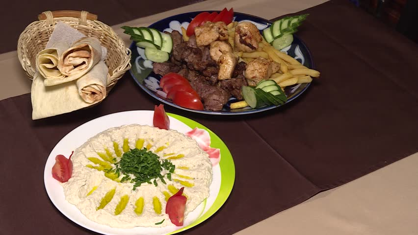 A man puts dishes with food on the table. Only hands and plates. Close-up of middle eastern platter of kebab, potatoes, hummus, vegetable salad, pita. Traditional oriental dishes