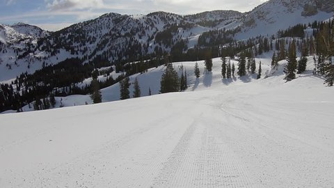Three expert skiers, a man and two women, pass camera fast as it follows them down a ski area in Utah's Wasatch Mountains.