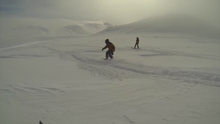 Two snowboarders ride down the slope, in the fog | Shutterstock HD Video #1010211695