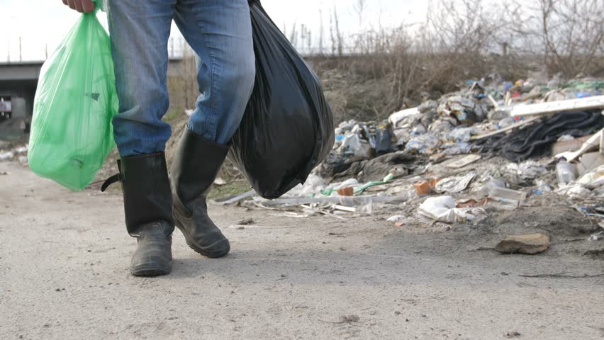 Close-up male legs in dirty boots waslking at garbage dump site. Homeless man holding trash bags full of plastic for recycling and scavenging at city landfill site. Steadicam shot