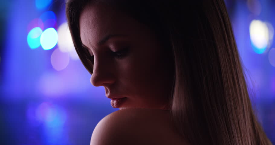 Dramatic side view close-up of beautiful woman on vibrant blurred background. Millennial woman in her 20s bathed in shadow looking dramatic with bokeh lights in background. 4k #1010220455