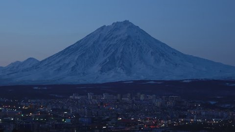 Winter night view of Kamchatka town scape - urban development of Petropavlovsk-Kamchatsky City on background cone of majestic active Koryak Volcano. Kamchatka Peninsula, Russian Far East, Eurasia.