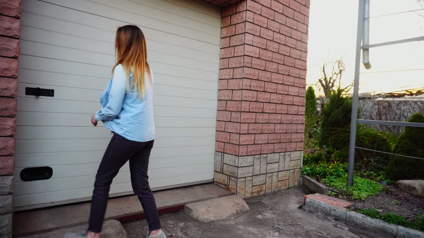 Female person opening white door with keys and showing place for car. Concept or renting house with big garage. Girl wears blue jeans shirt.