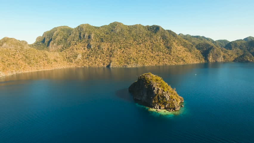 Aerial view: beach, tropical island, sea bay and lagoon, mountains with rainforest, Busuanga, Palawan. Seascape, tropical landscape. Azure water of lagoon. Aerial video. Philippines. 4K video Travel