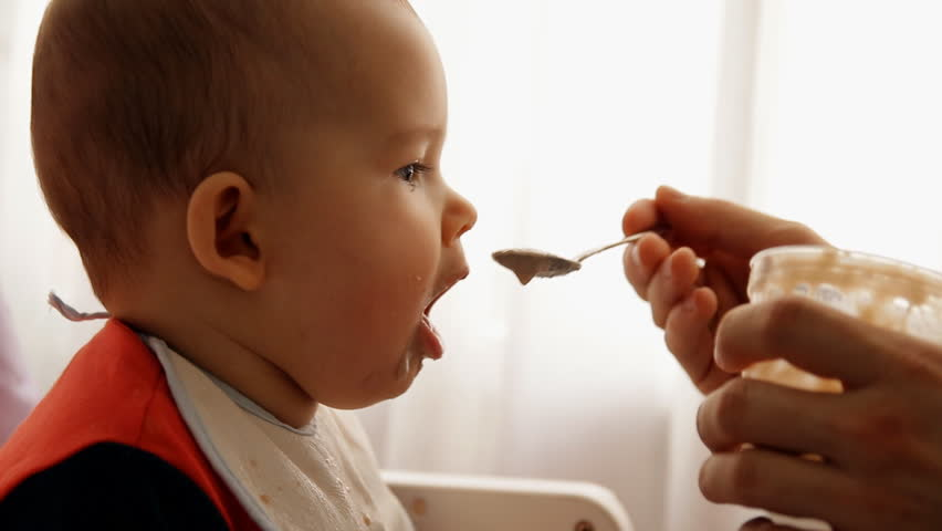 Slow motion of a young happy father feeds his son baby porridge.