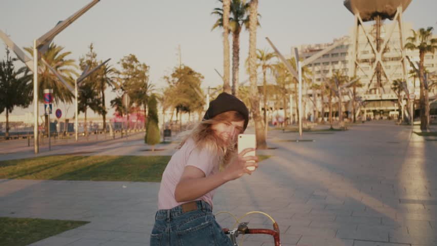 Happy, emotional smiling young millennial woman or hipster student teenager rides bike through park or beach promenade in beautiful sunset light, makes photos of camera on smartphone, excited travel
