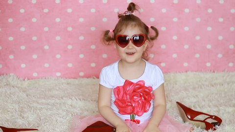 Cute little girl in red sunglasses in the shape of hearts sends air kisses.Pink background. Fashionista.