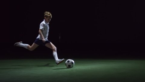 Junior soccer player running on artificial turf in indoor arena and kicking ball with power in low key lightning