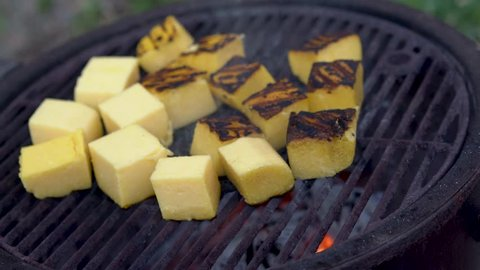 Wide shot of polenta on the grill with someone scraping them up and flipping them over.