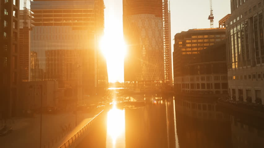Spectacular tracking sunset shot in the Canary Wharf docklands district, the financial heart of London, England, UK
