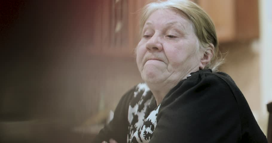 Old grandmother tells the stories sitting at the table | Shutterstock HD Video #1010429375