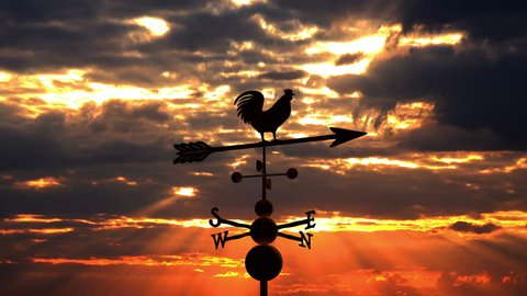 Weathervane cockerel floating against red sunset