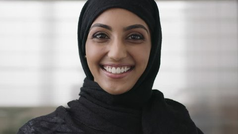 portrait of professional young muslim business woman looking at camera laughing cheerful wearing traditional headscarf in office background close up